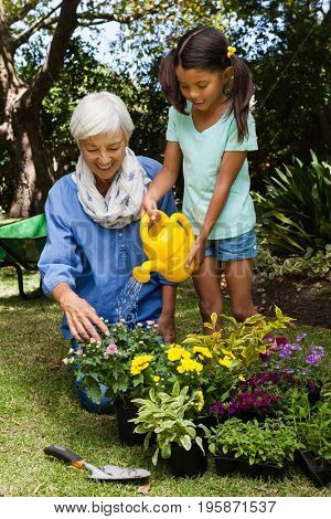 Senior woman looking at girl watering flowers in backyard