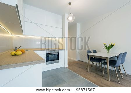 Modern kitchen interior design in white finishing with dinning table