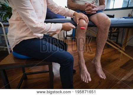Low section of female therapist examining knee with reflex hammer on male patient at hospital ward
