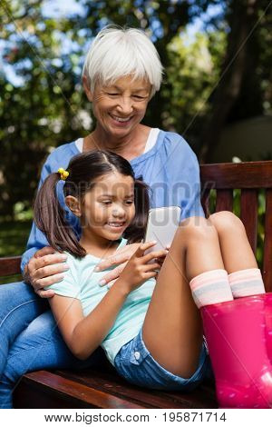 Smiling grandmother sitting with granddaughter using mobile phone on wooden bench at backyard