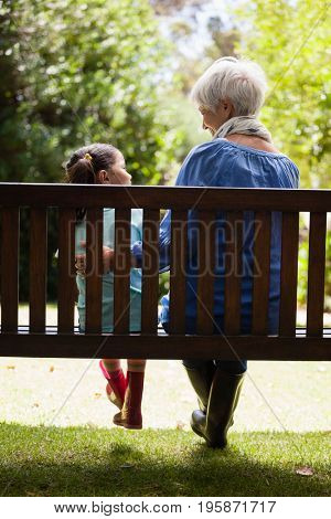 Rear view of grandmother and granddaughter sitting on wooden bench at backyard