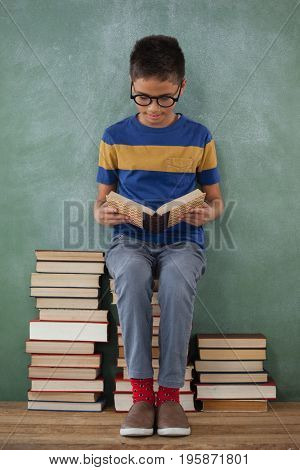 Schoolboy sitting on books stack and reading book against chalkboard