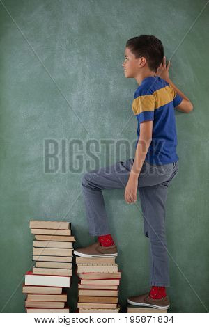 Schoolboy climbing steps of books stack against chalkboard