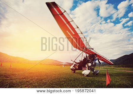 paraglider with a motor is standing on the ground, preparing for take-off. Against the backdrop of the mountains and sunset with glare. The concept of extreme entertainment with a parachute in the air.