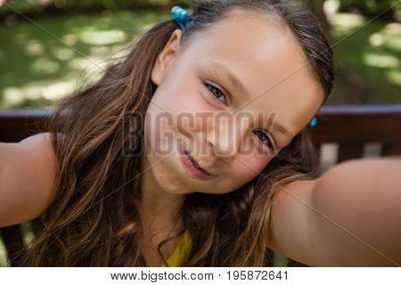 Portrait of playful girl making face at backyard