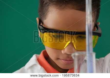 Attentive schoolboy experimenting against green background