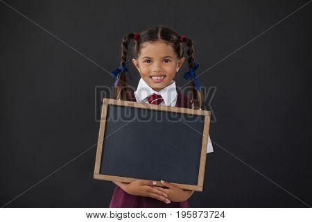 Portrait of schoolgirl holding blank slate against blackboard in classroom