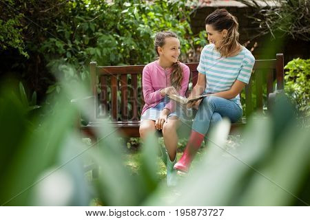 Happy mother and daughter looking at each other while sitting with novel on wooden bench in backyard