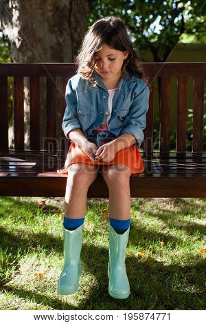Upset girl sitting on wooden bench while looking down at garden