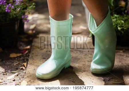 Low section of girl wearing green rubber boot standing on footpath at backyard
