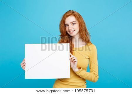 Business Concept - Close up Portrait young beautiful attractive redhair girl smiling showing blank sign. Blue Pastel Background.