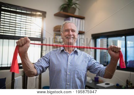 Portrait of smiling senior male patient pulling red elastic band at hospital ward