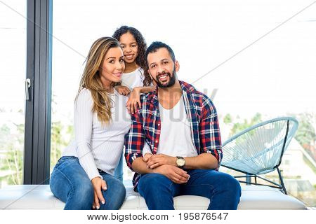 Young parents siting in front of the window while their daughter standing behind them
