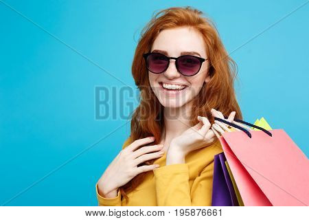 Shopping Concept - Close up Portrait young beautiful attractive redhair girl smiling looking at camera. Blue Pastel Background. Copy space.