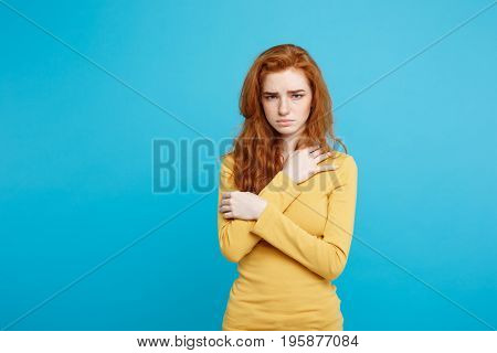Close up Portrait young beautiful attractive redhair girl feeling nervous looking at camera. Blue Pastel Background. Copy space.