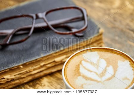 Coffee, old book and glasses. Latte with foam close up. Can coffee make you smarter.