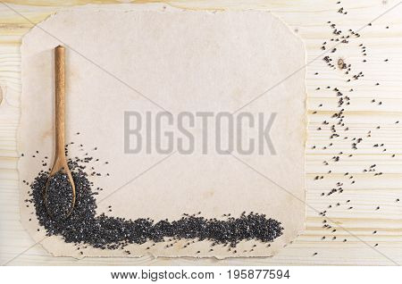 Chia seeds in spoon and paper for text on the wooden background top view