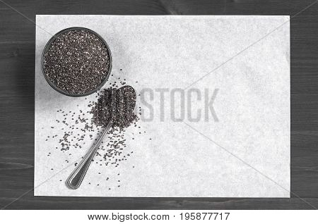 Chia seeds in bowl and paper for text on the dark wooden background top view