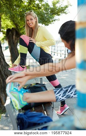 Pretty blonde runner stretching outdoors, smiling happy.