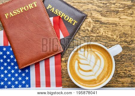 Coffee, passports and US flag. White latte cup top view. American citizenship requirements.