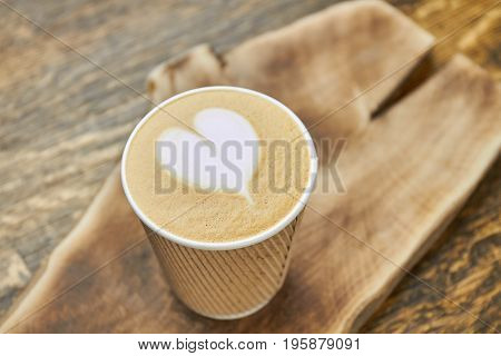 Heart latte art, paper cup. Coffee drink on blurred background. Love at first sip.
