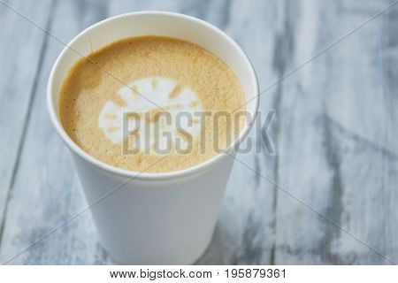 Clock latte art. Paper coffee cup, blurred background. Can caffeine slow down aging.