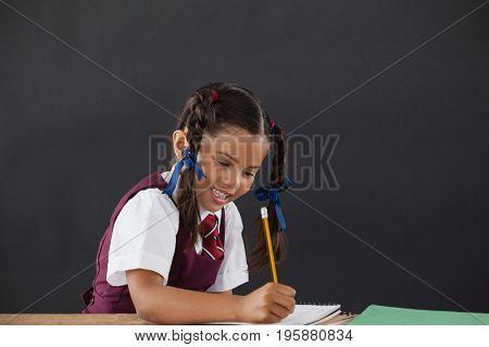Attentive schoolgirl doing her homework against chalkboard