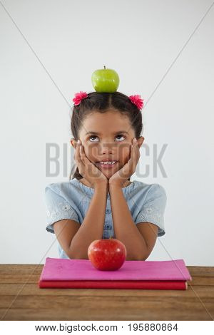 Adorable schoolgirl sitting with green apple on her head against white background