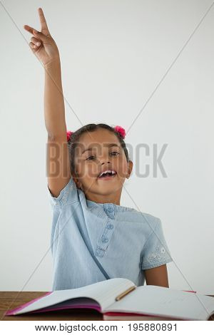 Young girl raising her hand against white background
