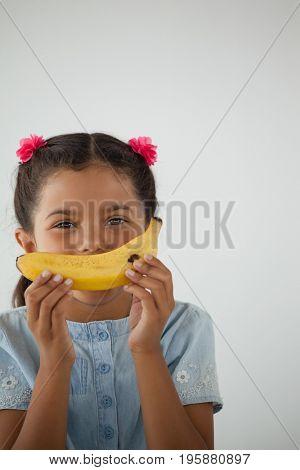 Adorable schoolgirl having breakfast against white background