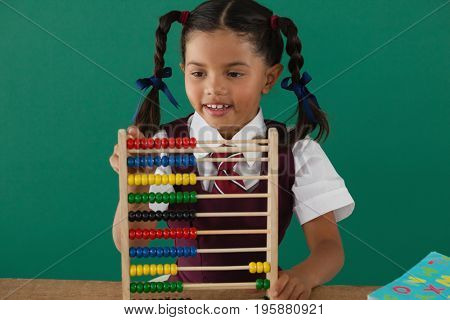 Schoolgirl using abacus against chalkboard in classroom