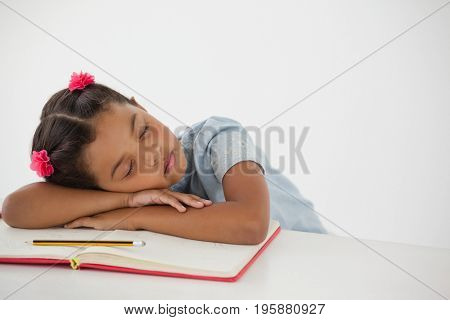 Young girl sleeping with her head on desk against white background