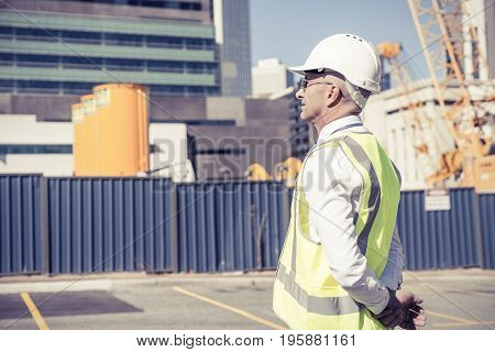 Engineer man in helmet and jacket controlling outdoor construction site