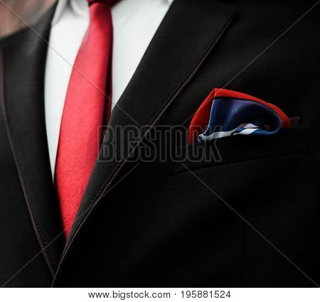 Closeup of elegant formal business suit with dark grey jacket with handkerchief in the pocket shirt and necktie