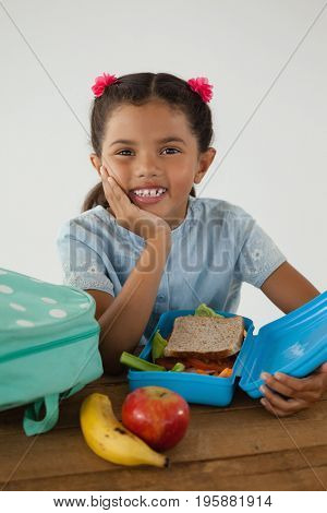 Portrait of schoolgirl sitting with tiffin box against white background