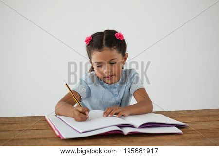 Portrait of young girl writing in her book against white background