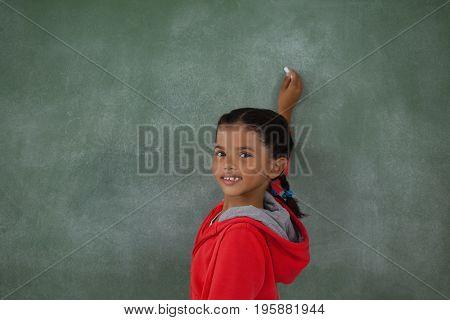 Portrait of young girl writing on chalk board