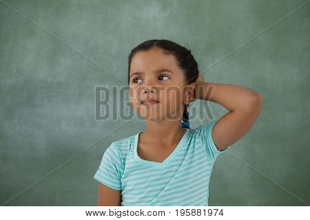 Thoughtful young girl against chalk board
