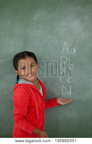 Portrait of young girl gesturing over chalk board