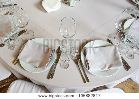 Serving festive dining event with glasses and plates for consumers - top view. Cutlery for people in the restaurant.