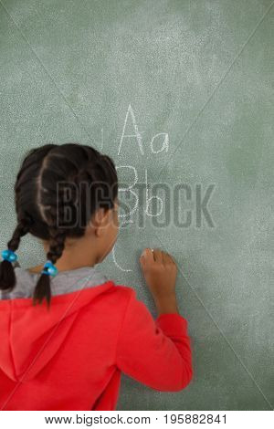 Description Young girl writing on chalk board