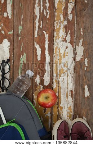 Bagpack, water bottle, apple, shoes and spectacle on wooden background