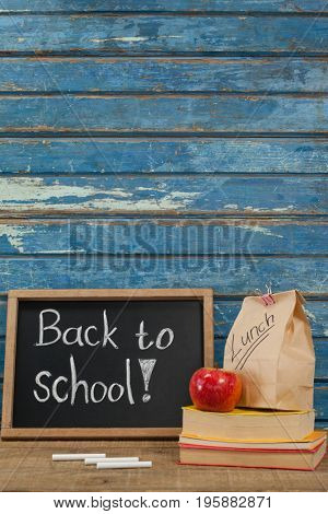 Apple, lunch bag, books and slate with back to school text against blue wooden background