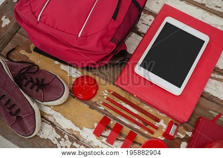Bagpack, shoes, digital tablet and stationary on wooden background