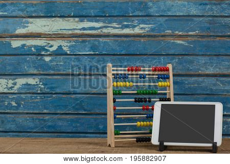 Abbacus game and digital tablet against blue wooden background