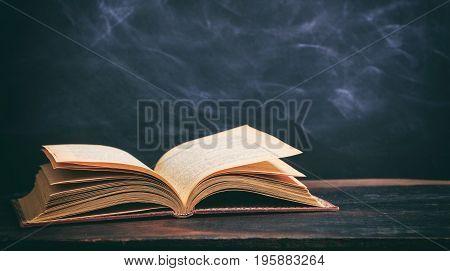 Vintage Book On Blackboard Background
