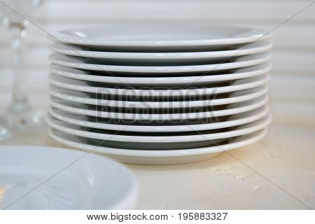 A stack of clean white plates on a white background. Cutlery for eating.