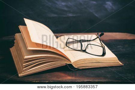 Old Book And Eye Glasses On Blackboard Background