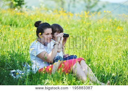 Mother with her young son looking through binoculars sitting on the grass in the mountains