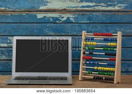 Abbacus game and laptop against blue wooden background